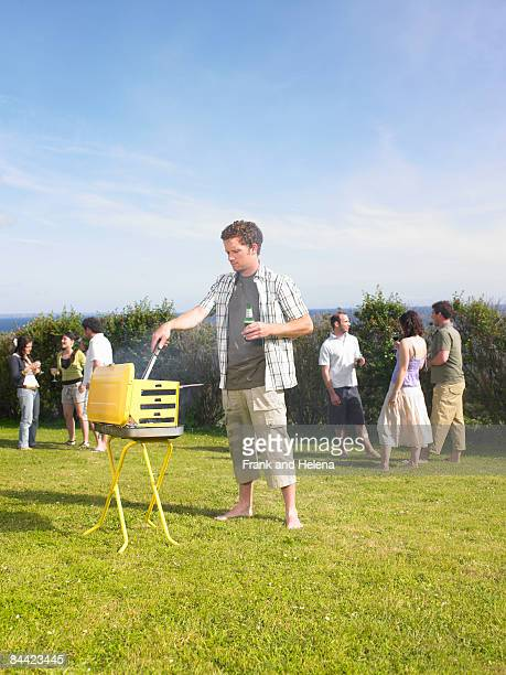 Man tending barbecue at a party