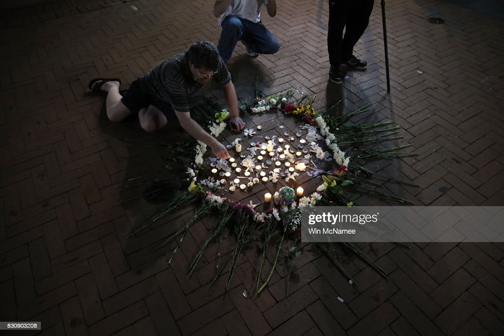 A man tends a makeshift candlelight vigil for those who died and were injured when a car plowed into a crowd of anti-fascist counter-demonstrators marching near a downtown shopping area August 12, 2017 in Charlottesville, Virginia. The car allegedly plowed through a crowd, and at least one person has died from the incident, following the shutdown of the 'Unite the Right' rally by police after white nationalists, neo-Nazis and members of the 'alt-right' and counter-protesters clashed near Emancipation Park, where a statue of Confederate General Robert E. Lee is slated to be removed.