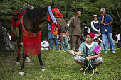 A man tends to a horse while waiting for a procession to start during the Soma Nomaoi festival at the Nakamura Shrine in Soma Fukushima Prefecture...