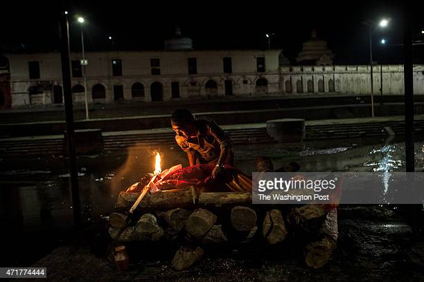 A man tends to the body of a relative at Pasupatinath Aryaghat a crematorium and holy site in Kathmandu Nepal on Wednesday April 29 2015 Thousands of...