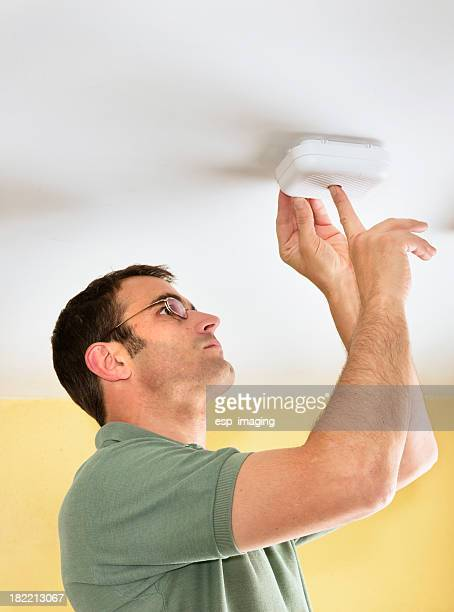Homme tests d'un détecteur de fumée avec alarme incendie