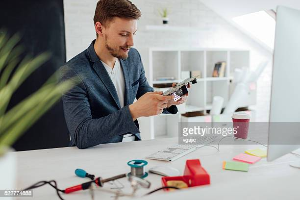 Man Testing Circuit Board In His Office.