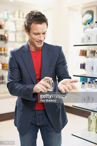 Man testing cologne in store