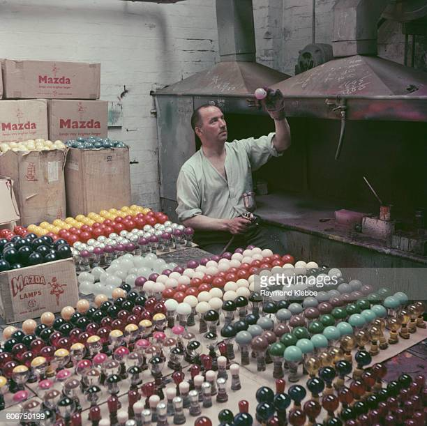 A man testing coloured Mazda lightbulbs at an electric light factory in Blackpool UK January 1956 Original Publication Picture Post 8603 Electric...