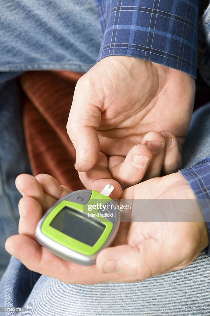 Man Testing His Blood Sugar With Glucometer : Stock Photo