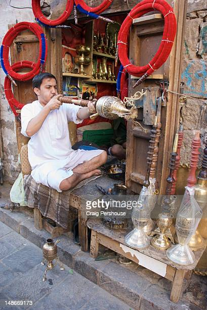 Man testing newly-made hookah (waterpipe) outside his tiny workshop in Souk al-Milh.