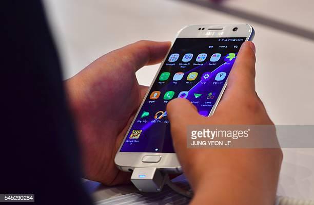A man tests Samsung Electronics' Galaxy S7 at its showroom in Seoul on July 7 2016 Samsung Electronics on July 7 flagged its biggest operating profit...