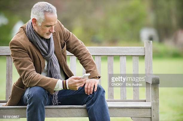 Man text messaging on a mobile phone in a park