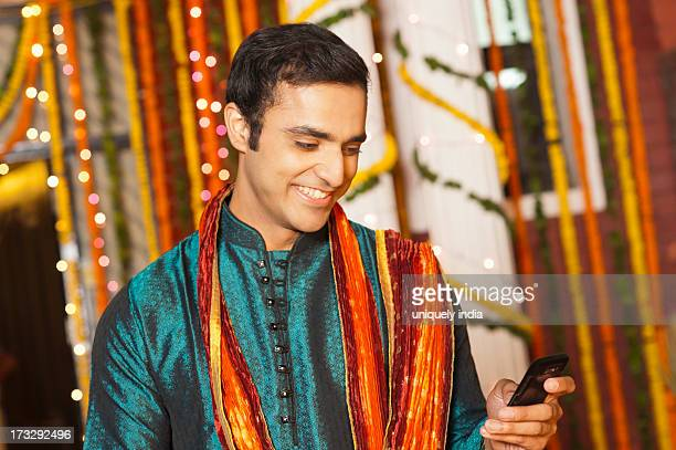 Man text messaging on a mobile phone on Diwali
