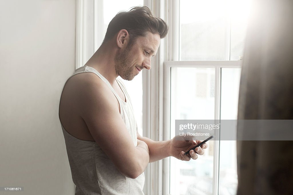 Man texting at window in morning : Stock Photo