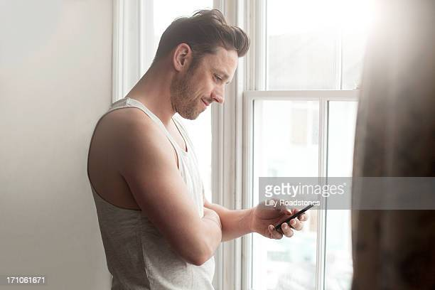 Man texting at window in morning