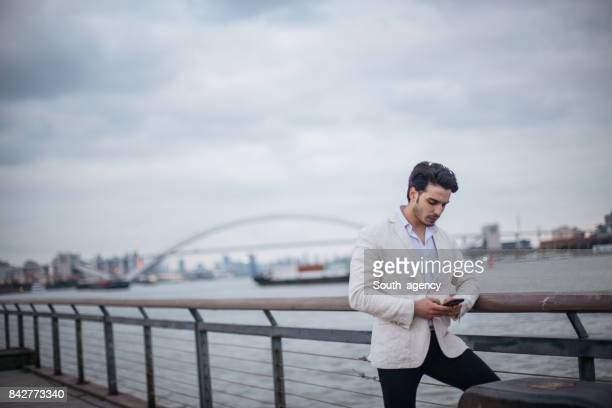 Man texting by the river