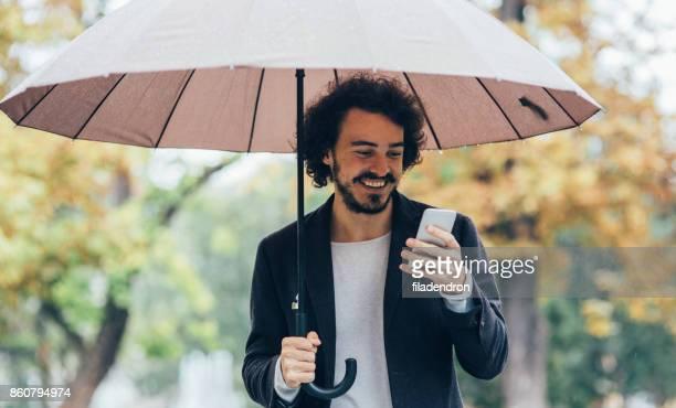 Mann SMS im Regen