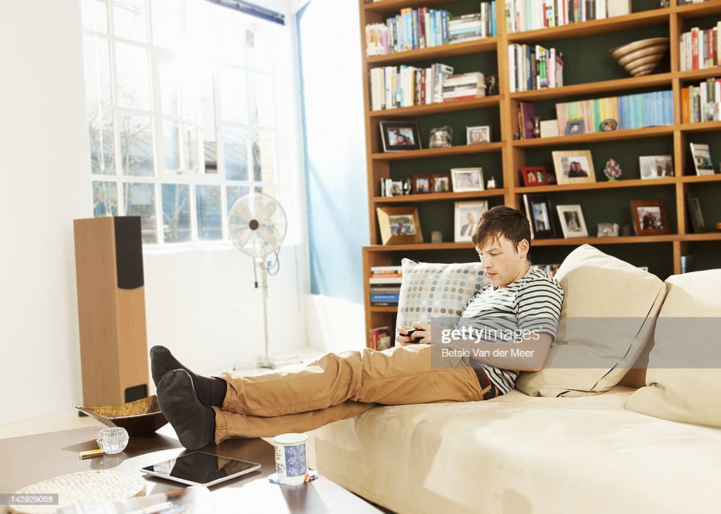 Man texting on mobile phone in livingroom. : Stock Photo