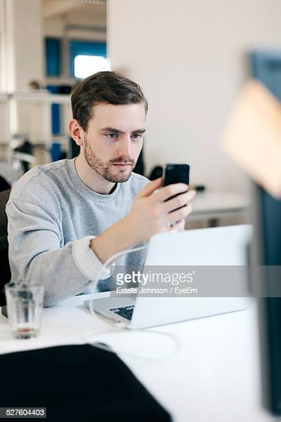 Man Texting On Mobile Phone In Office
