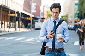 Businessman using smartphone and holding paper cup ina urban scene. Worried businessman in walking on the road and messaging with phone. Young man text messaging through cell phone while walking on th