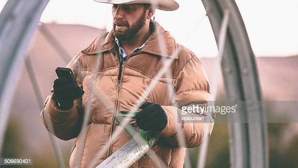 Uomo di SMS sul telefono mentre si lavora con attrezzatura per l'irrigazione