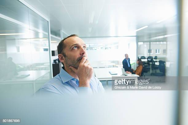 Man thinking, people in background