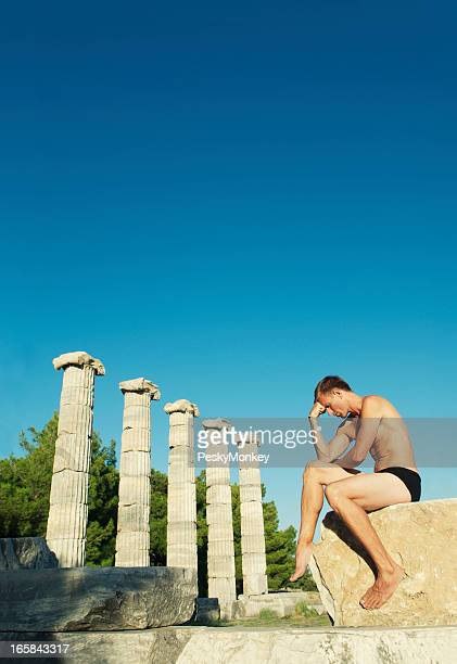Man Thinking Sits Next to Row of Columns