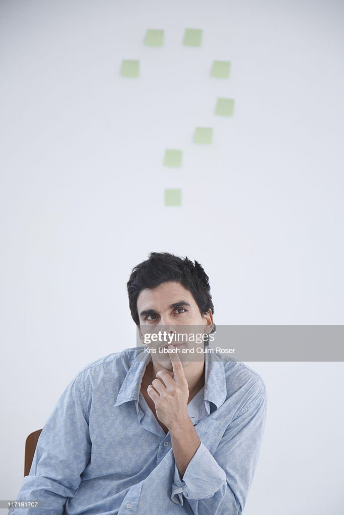 Man thinking with post-it note question makr behind him