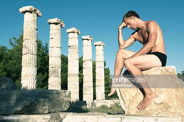 Man Thinks On Rock Next To Ancient Columns