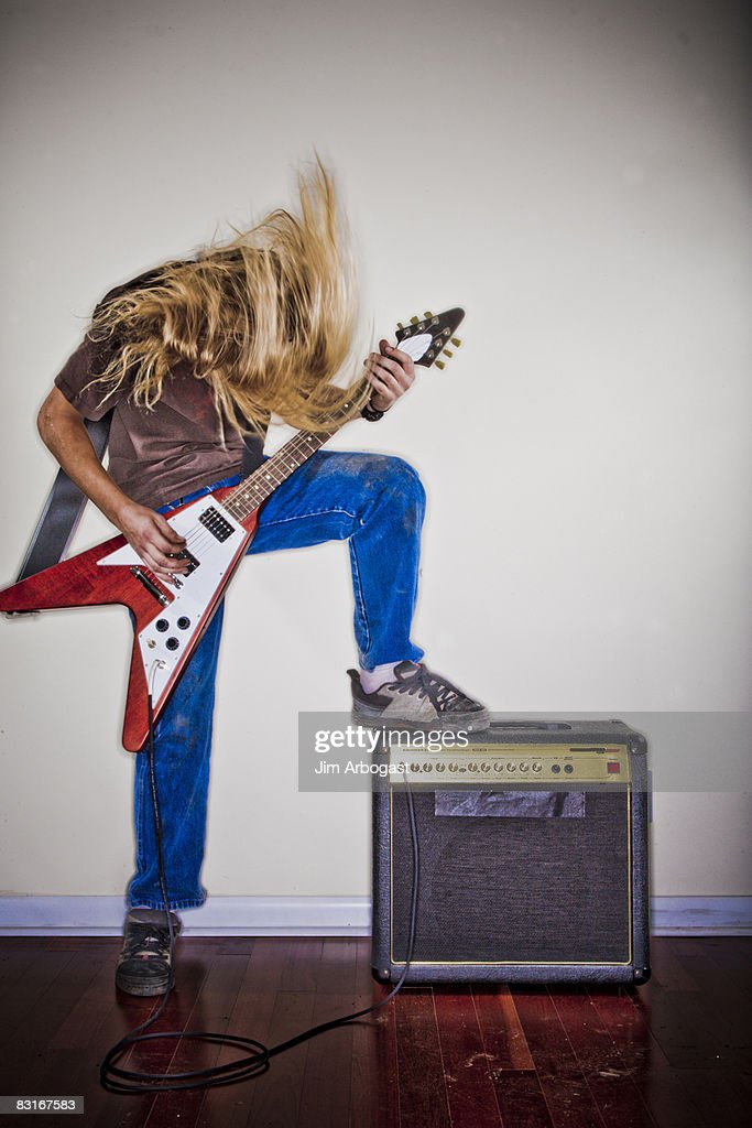 Man thrashes head while playing guitar. : Stock Photo