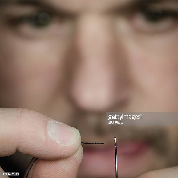 Man threading needle