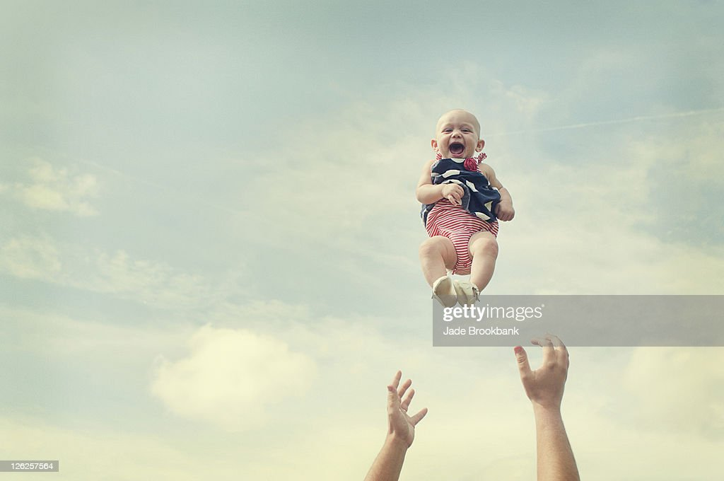 Man throwing baby in air : Foto de stock