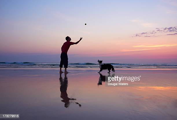 Man throwing ball for dog.