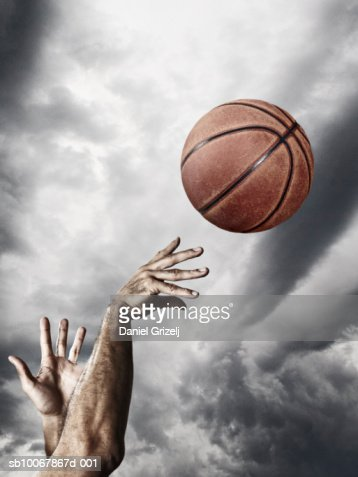 Man throwing basketball in air, close-up of hands