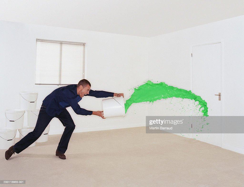 Man throwing bucket of green paint at door : Stock Photo