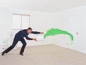 Man throwing bucket of green paint at door