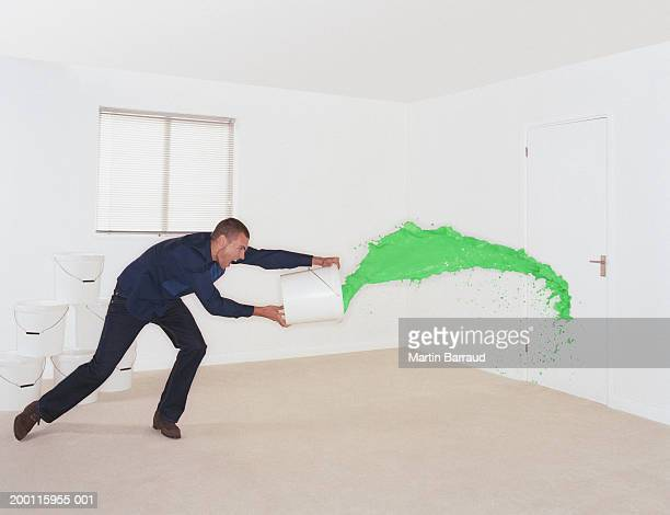 Man throwing bucket of green paint at door