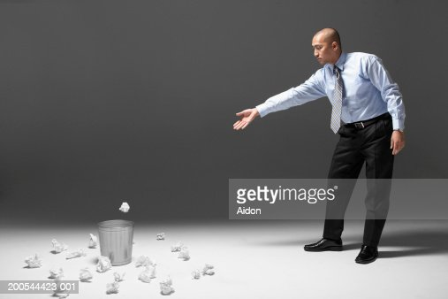 Man throwing crumpled paper into waste basket, studio shot : Stock Photo