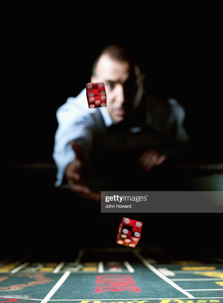 Man throwing dice across gaming table (focus on dice) : Stock Photo