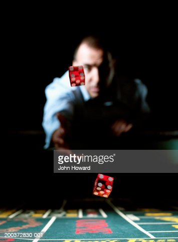 Man throwing dice across gaming table (focus on dice)