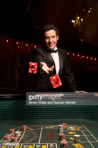 Man throwing dice at craps table : Stock Photo