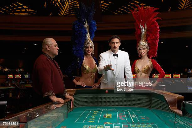 Man throwing dices at roulette table, two dancers and senior casino worker next to him