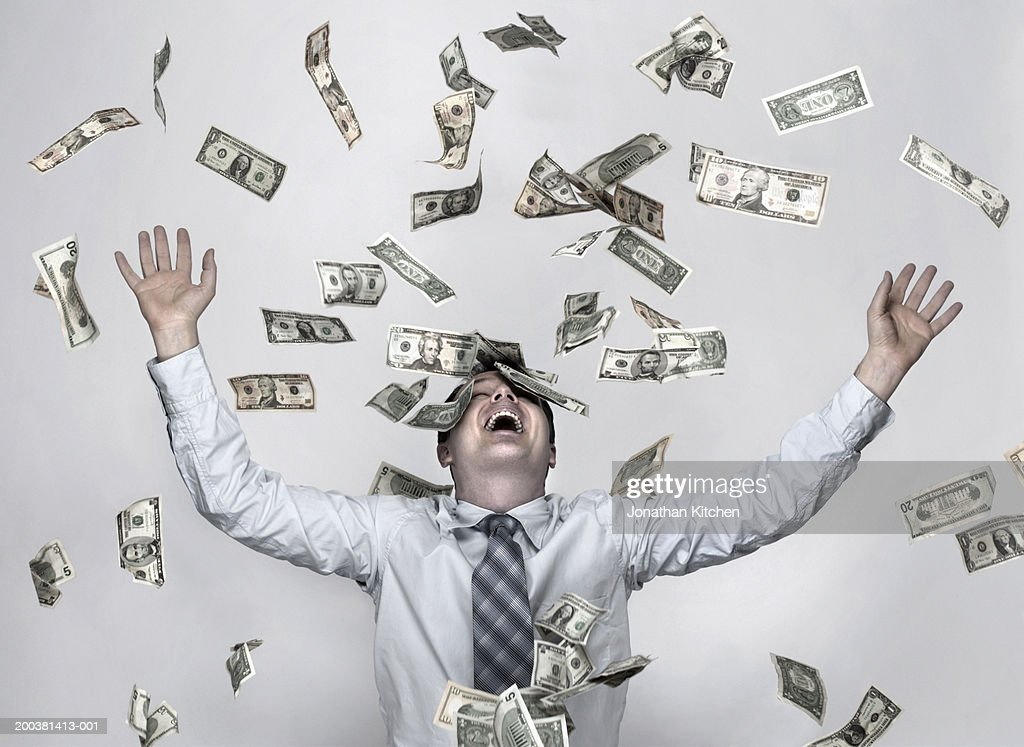 Man throwing dollar bills in the air, arms raised in celebration : Stock Photo
