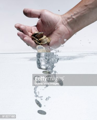 Man throwing money in water : Stock Photo