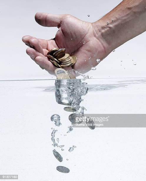 Man throwing money in water
