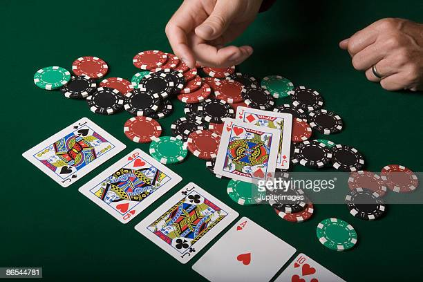Man throwing playing cards onto pile of poker chips