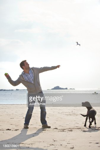 Man Throwing the Ball for his Dog on the Beach