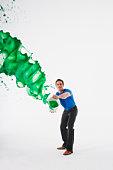 Man throwing tin of green paint, studio shot