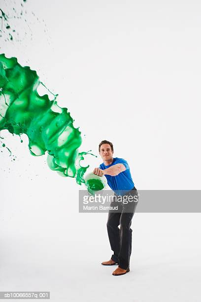 Man throwing tin of green paint, studio shot
