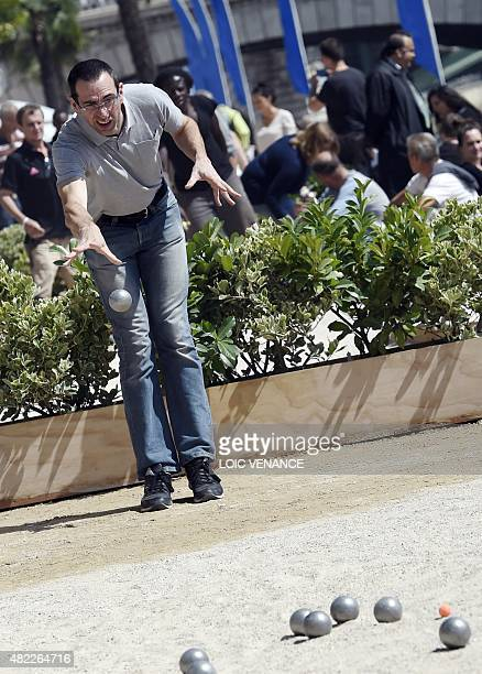 A man throws a ball as he plays petanque during the 'Paris Plages' event in central Paris on July 29 2015 Paris Plages during which temporary...