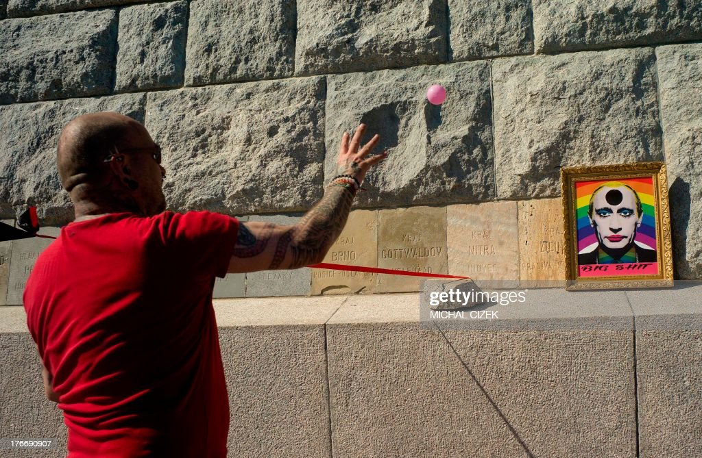 A man throws a ball on picture of the Russian president Valdimir Putin during the third gay pride festival in the Czech capital Prague on August 17, 2013.