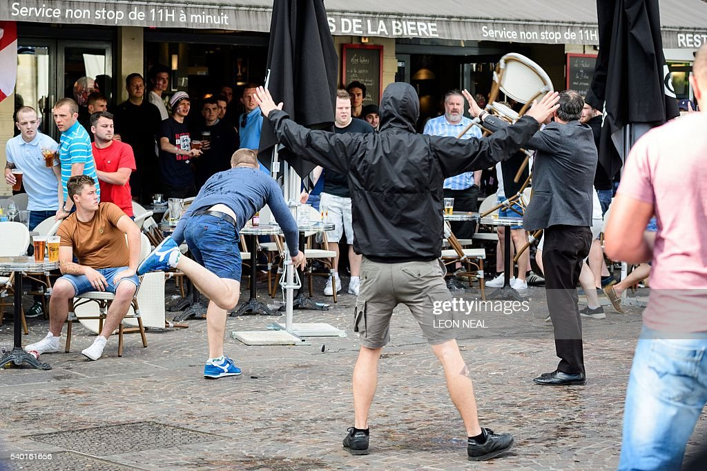 TOPSHOT A man throws a chair as a small group of Russian men provoke a group of England supporters in the centre of Lille on June 14 three days after...