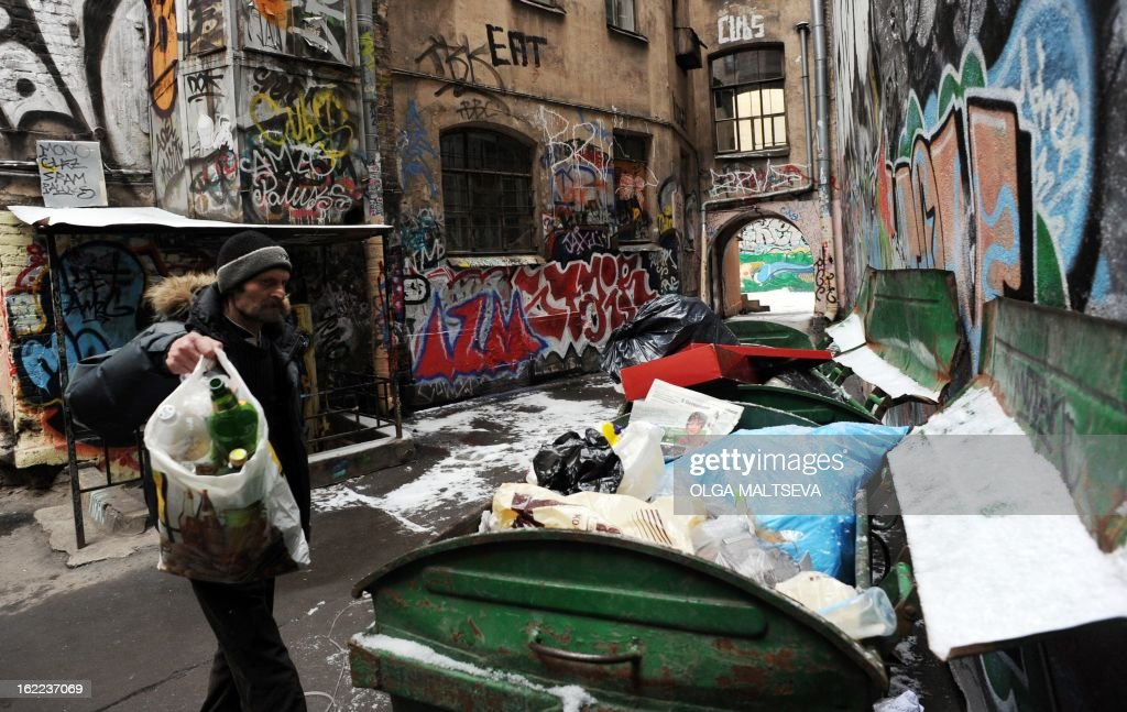 A man throws a garbage bag into a trash box in a courtyard in Russia's second city of St. Petersburg, on February 20, 2013.