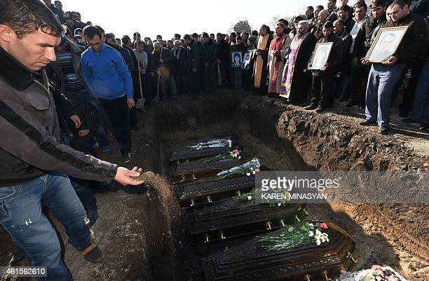 A man throws a handful of soil on coffins of victims during a funeral ceremony held for the six members of the same family allegedly killed by...